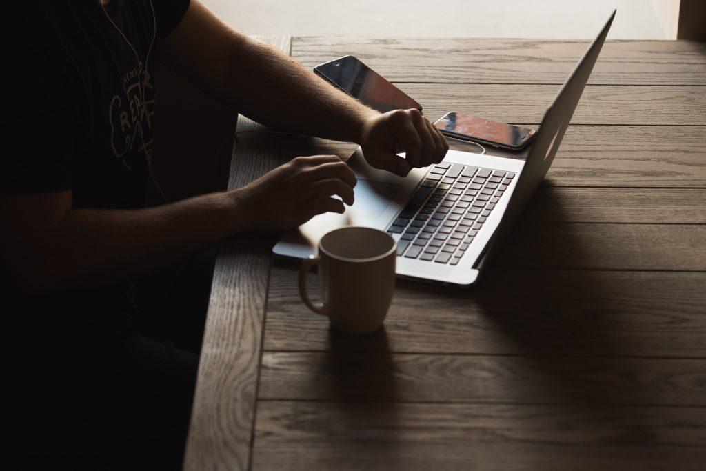 Un bărbat stând în fața unui laptop cu o cana și un telefon mobil conectat prin cablu
