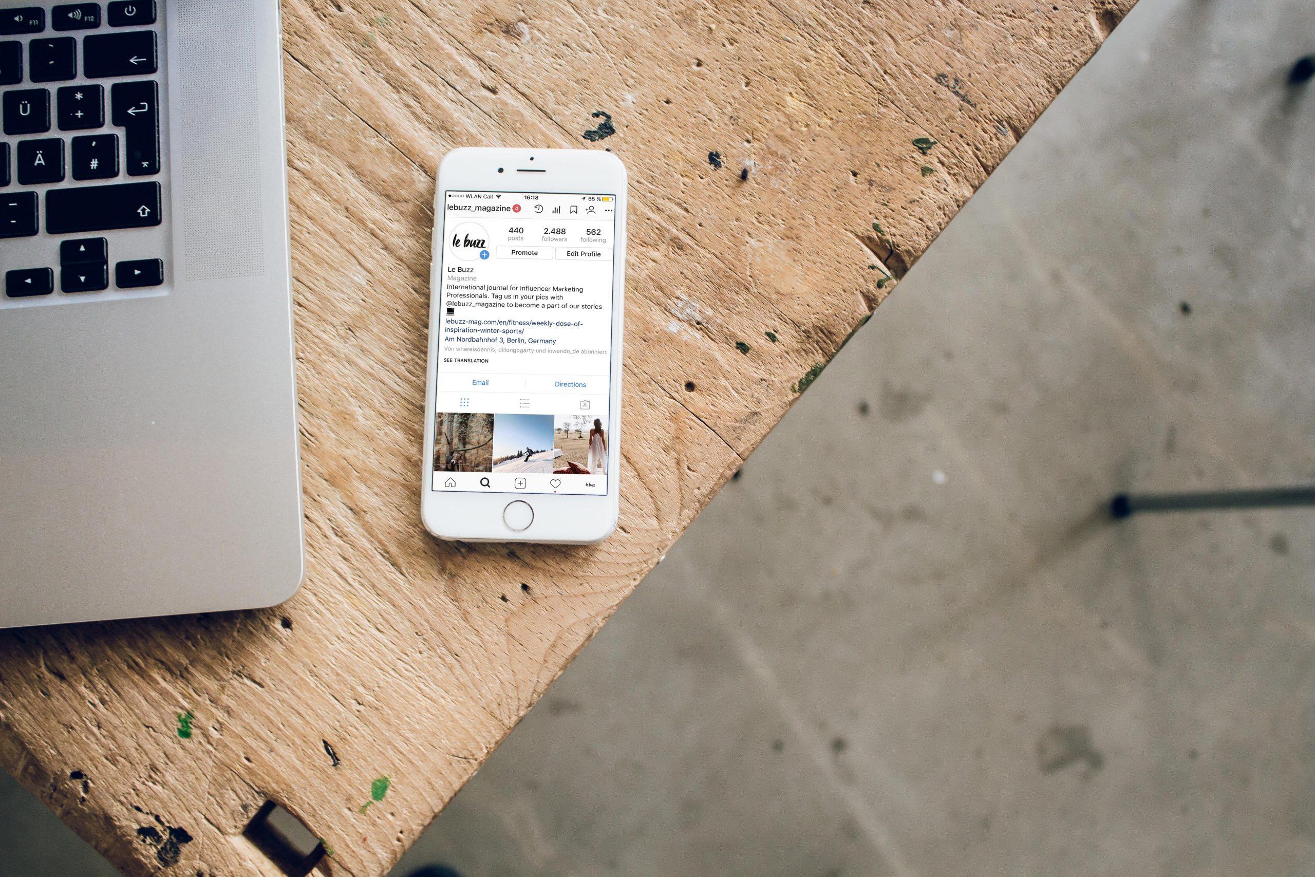 Smartphoen deschis pe Instagram asezat pe masa langa laptop