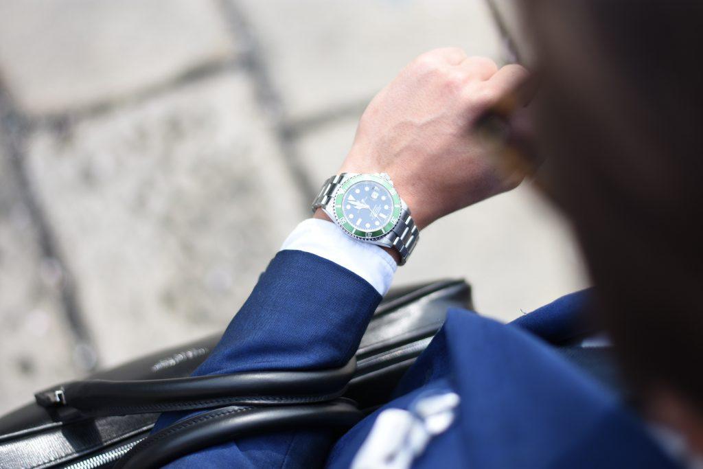 Bărbat îmbrăcat la costum se uită la ceas