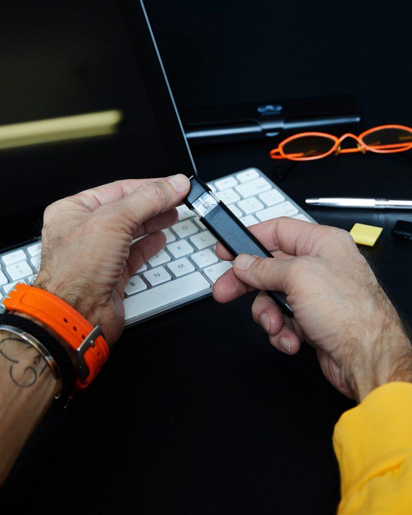 Un bărbat ține în mână țigara electronică YOOP