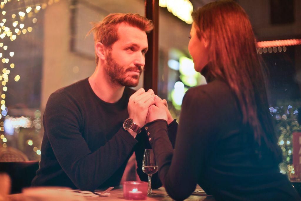 Bărbat și femeie îmbrăcați în negru la masa unui restaurant se țin de mâini
