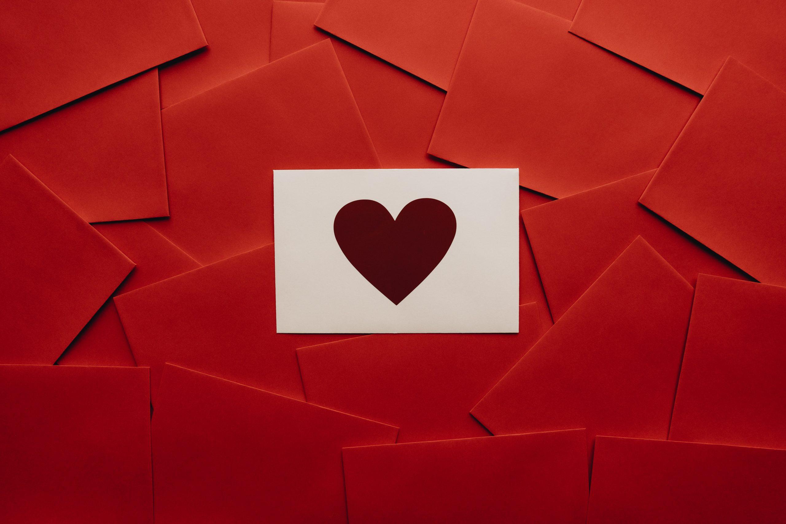 Gramada mare de plicuri rosii si un plic alb cu inimioara deasupra