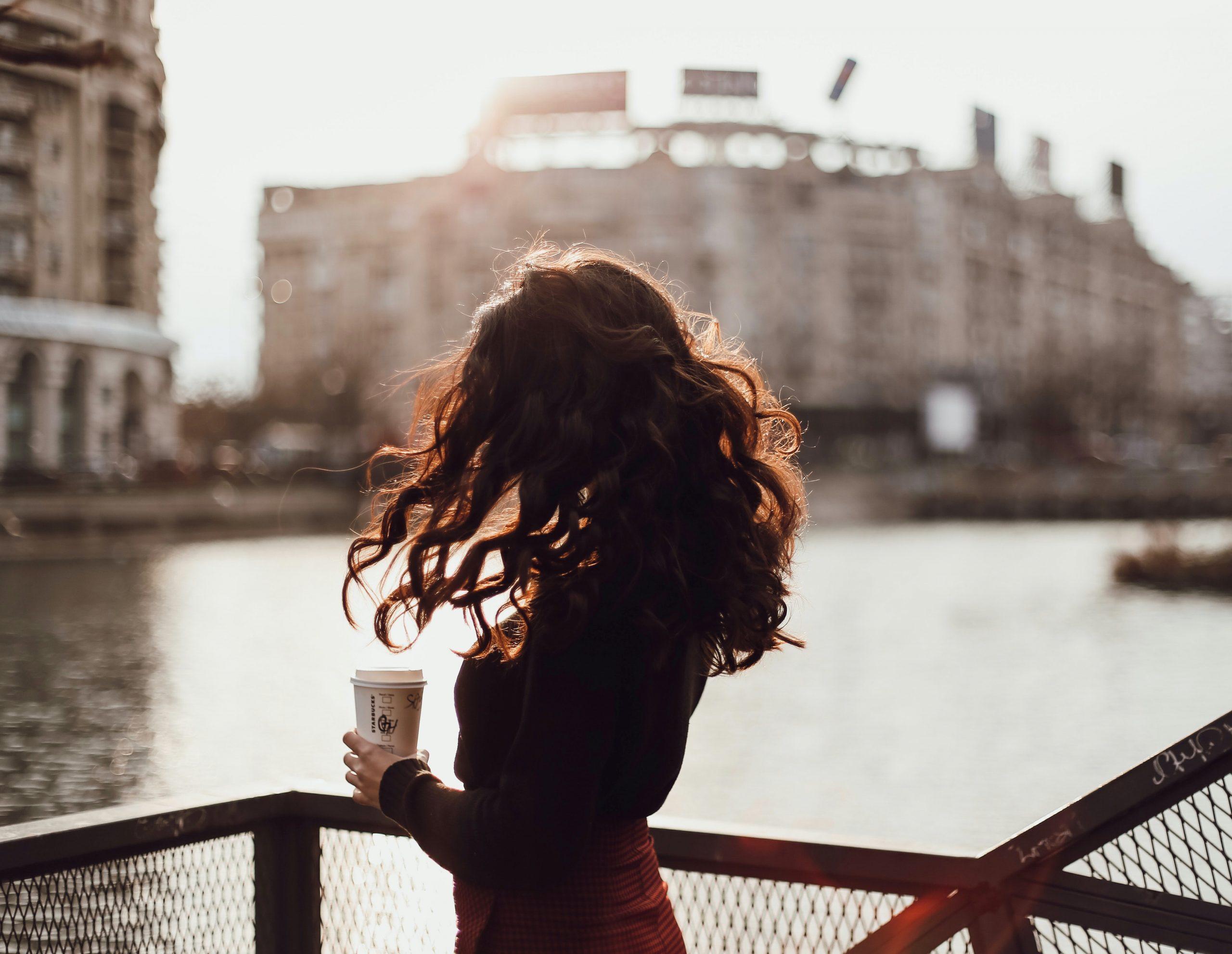 Fata cu spatele cu o cafea în mână stând pe podul peste Dâmbovița