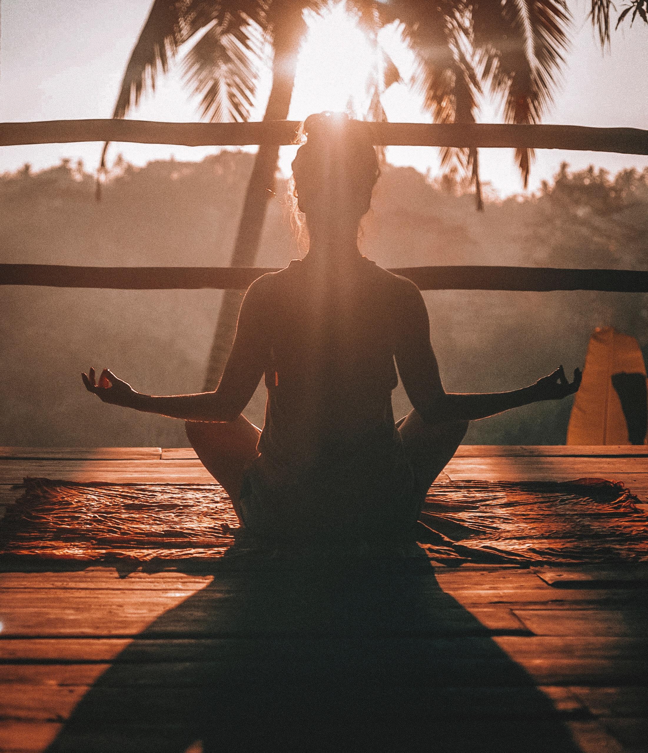 Fata care mediteaza in pozitie de yoga pe balcon