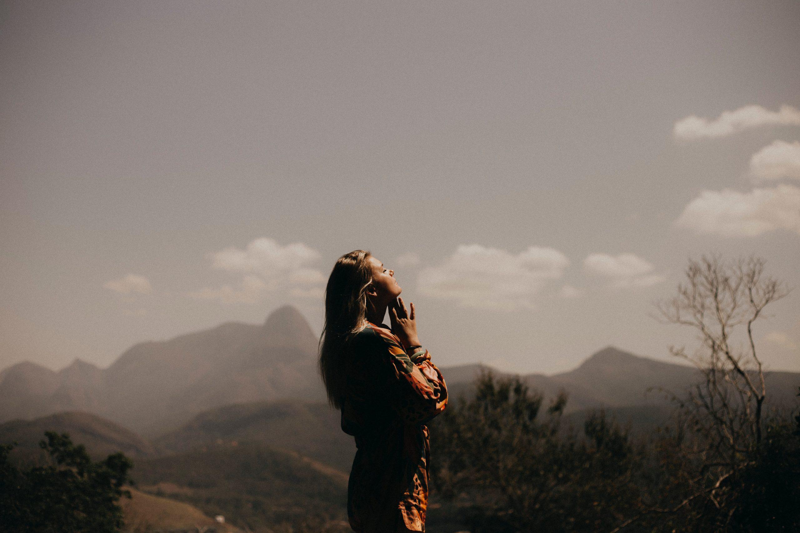 Fata stând in picioare în natura uitându-se spre cer