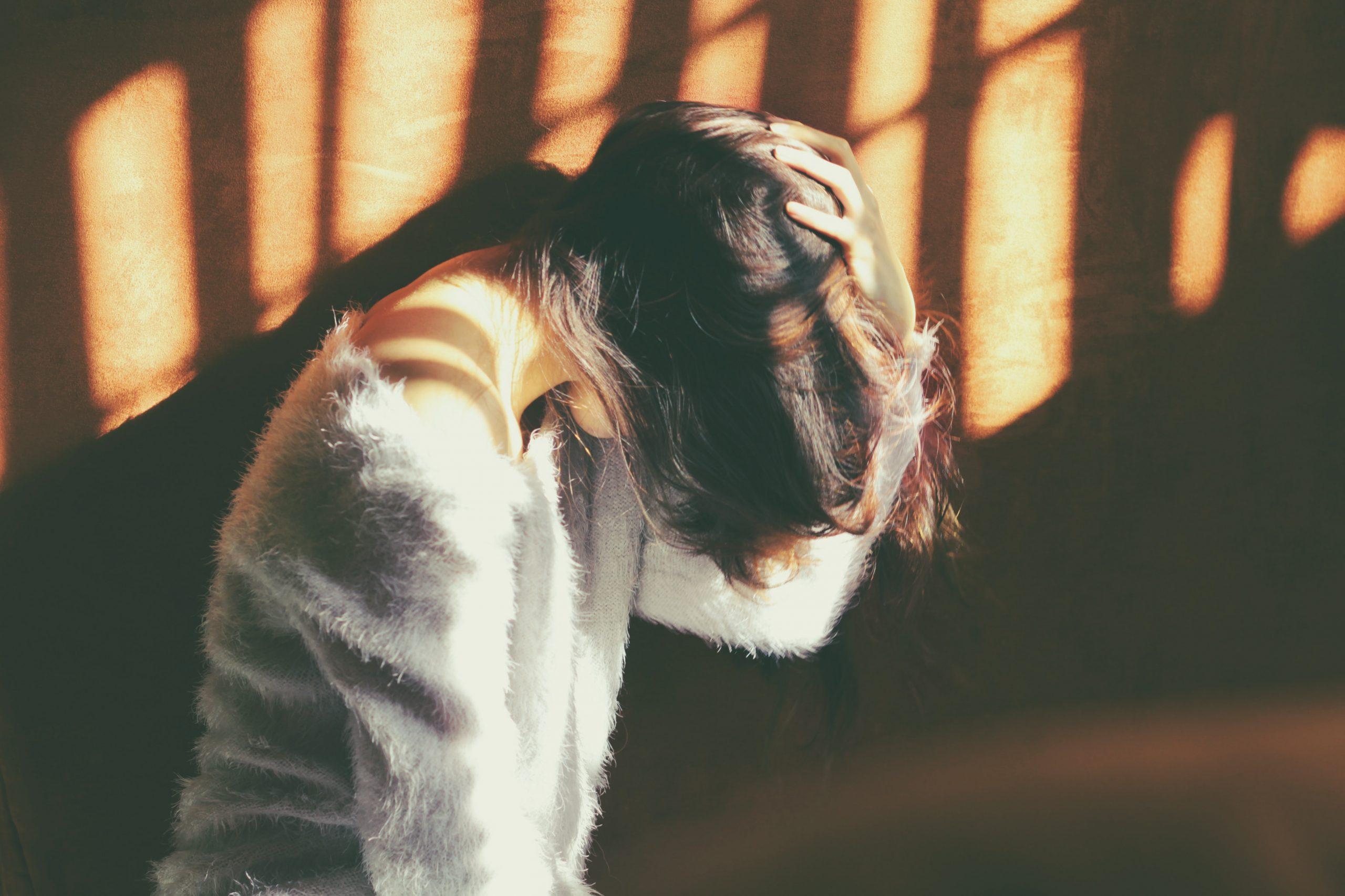 Fata rezemata de perete care se tine de cap ca si cum ar manifesta o durere greu de suportat
