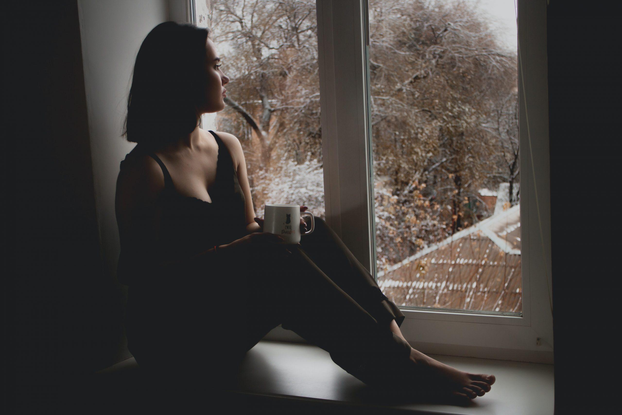 Fata care sta pe pervazul geamului uitandu-se trista afara